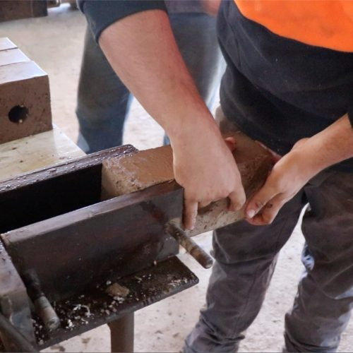 inserting hand made brick into cutting moulds